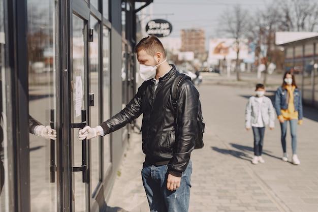Man in een masker staande op straat Gratis Foto