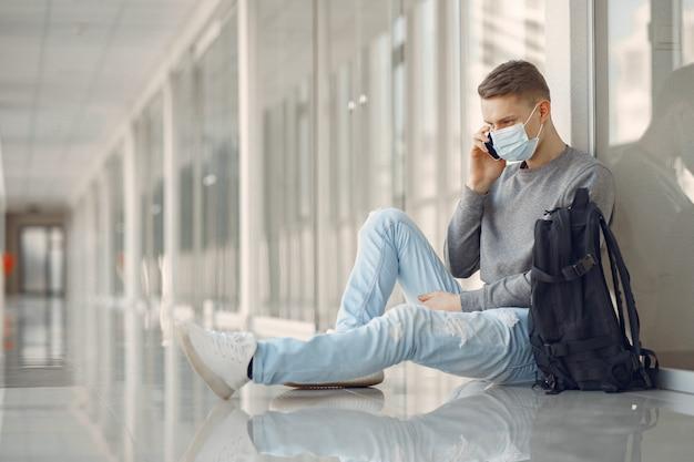 Man in een masker zitten in de hal van het ziekenhuis Gratis Foto
