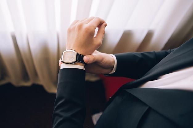 Man in een pak draagt een horloge. een man in een zwart pak. man kijkt naar de tijd. man in een pak. jonge kerel draagt horloges. Premium Foto