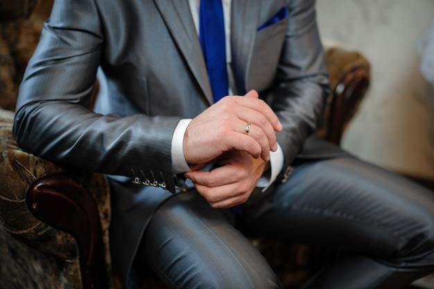 Man in een pak zittend in een stoel en zet manchetknopen Premium Foto