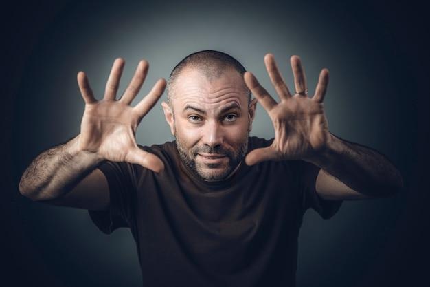 Man in een shirt met open handpositie alsof hij magie uitvoert. Premium Foto