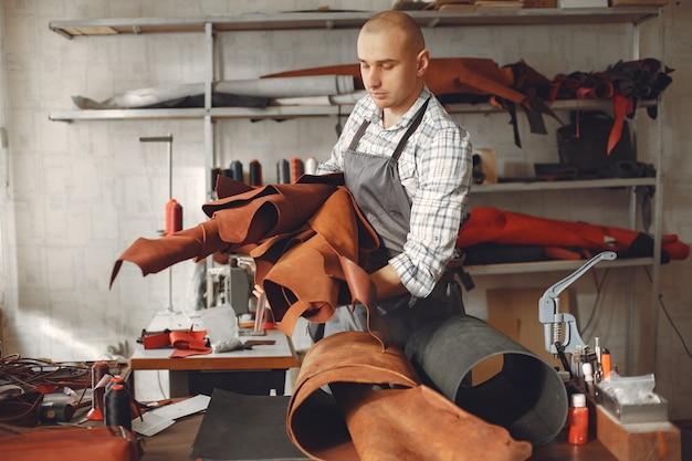 Man in een studio maakt lederwaren Gratis Foto