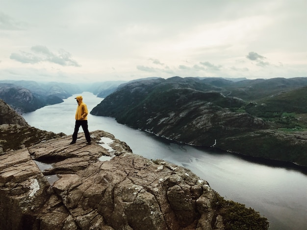Man in geel inter jassen stond voor een prachtig landschap Gratis Foto