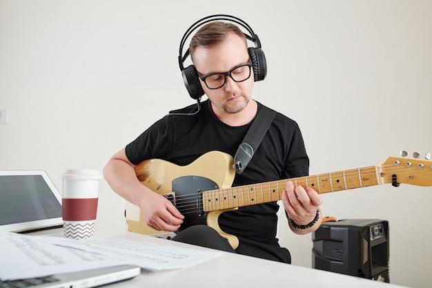 Man in glazen gitaar spelen Premium Foto