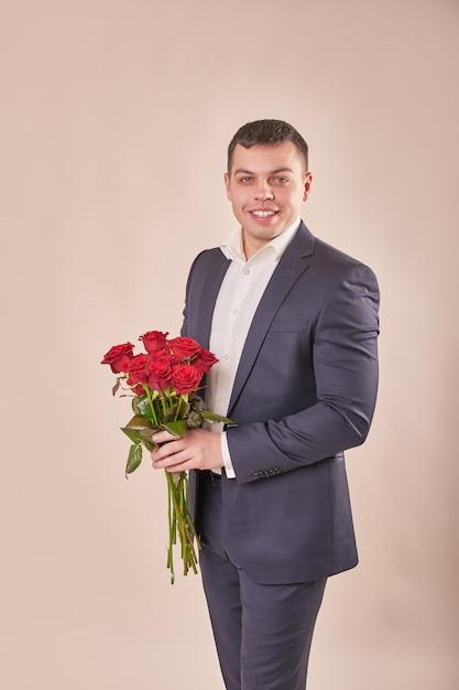Man in grijs pak met rode rozen Premium Foto