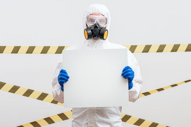 Man in hazmat pak met een leeg bord Gratis Foto