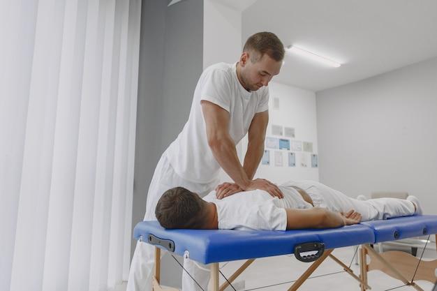 Man in het medische kantoor. fysiotherapeut is weer aan het revalideren. Gratis Foto