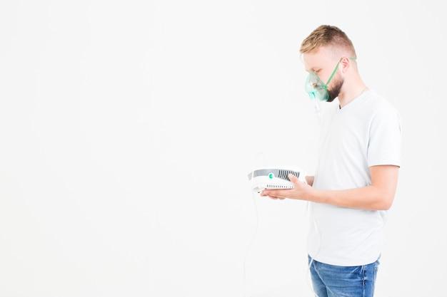 Man in het wit met vernevelaar Gratis Foto