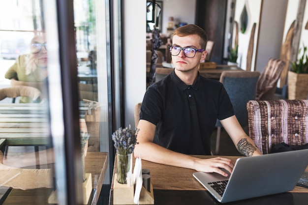 Man in het zwart die op laptop werkt Gratis Foto