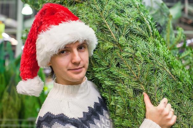 Man in kerstmuts ã â¡hristmas boom kopen en duimen opdagen Premium Foto
