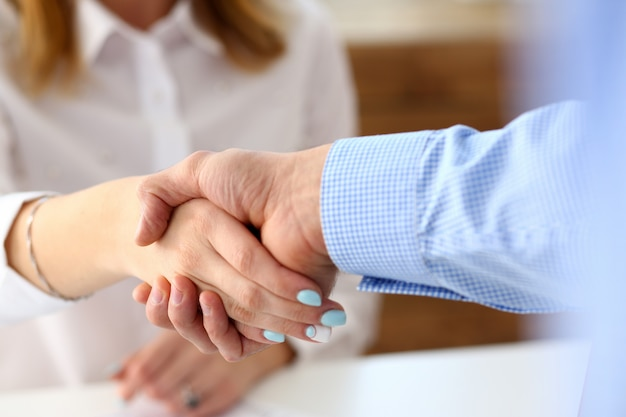 Man in pak en stropdas geven hand als hallo in kantoor Premium Foto