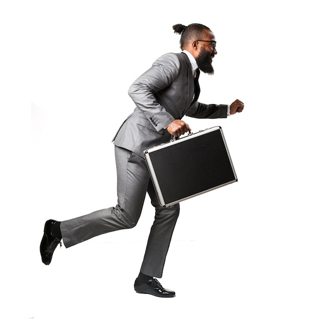 Man in pak lopen met een aktetas Gratis Foto