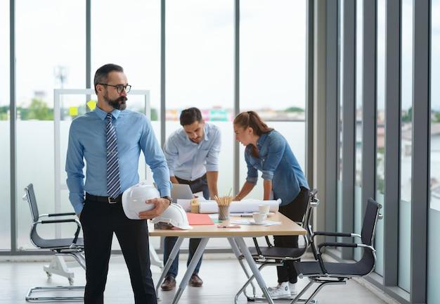 Man in pak met bouwhelm in de hand. ingenieur of arbeidersconstructie Premium Foto