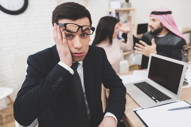Man in pak op kantoor met arabische man en vrouw. Premium Foto