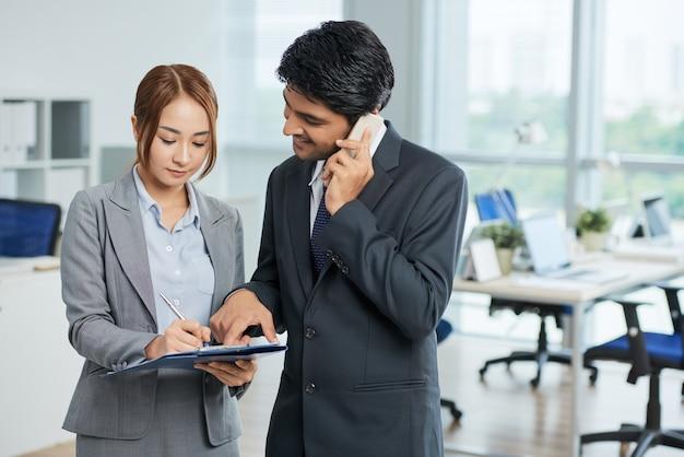 Man in pak praten over telefoon en vrouw maken van aantekeningen Gratis Foto