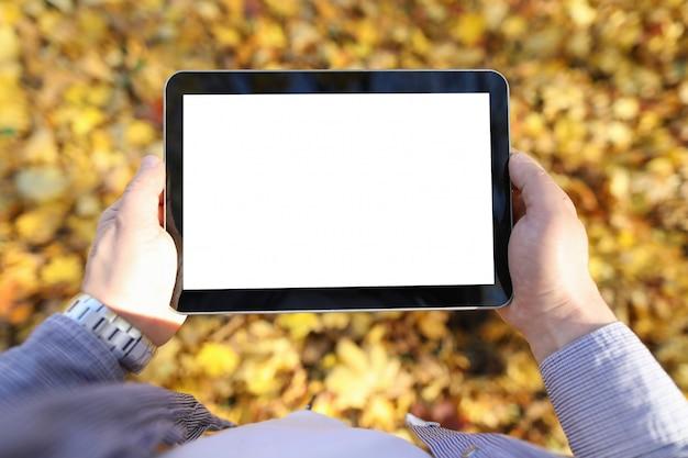 Man in park houdt digitale tablet Premium Foto
