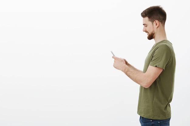Man in profiel met baard die smartphone vasthoudt en glimlachend opgewonden als interessant online spel via mobiele telefoon speelt, internet gebruikt om contact op te nemen met vriend, coole meme verzendt over witte muur Gratis Foto