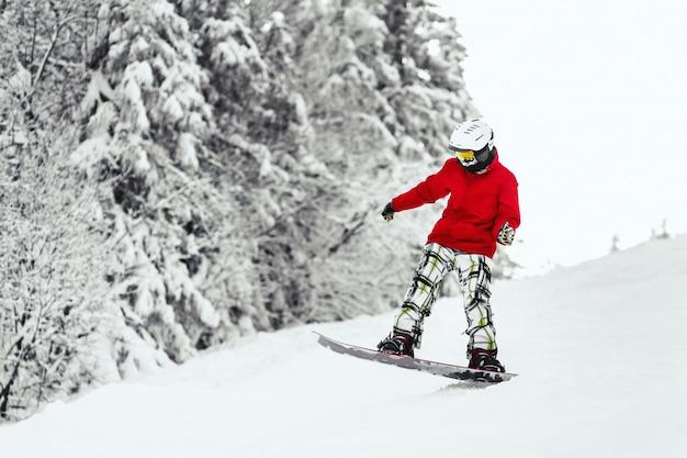 Man in rode ski-jas gaat de heuvel af op zijn snowboard Gratis Foto