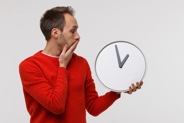 Man in rode trui met grote ronde klok, in shock bedekt zijn mond met zijn hand. gebrek aan tijd Premium Foto