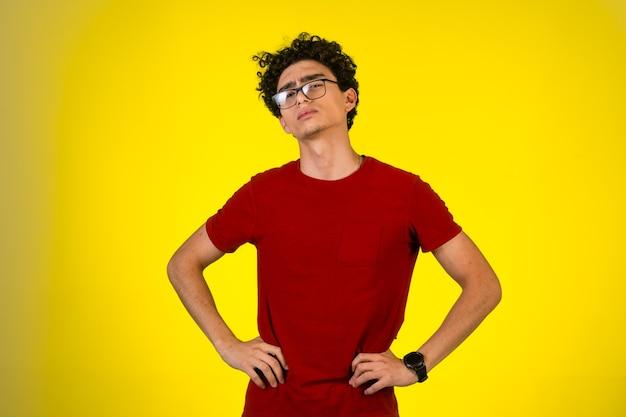 Man in rood shirt legde zijn handen op zijn middel. Gratis Foto