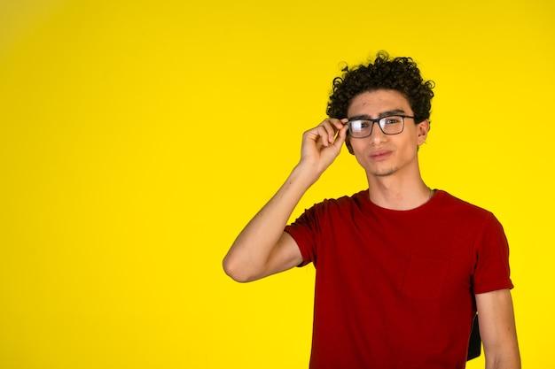 Man in rood shirt zijn bril aan te raken en flirten Gratis Foto