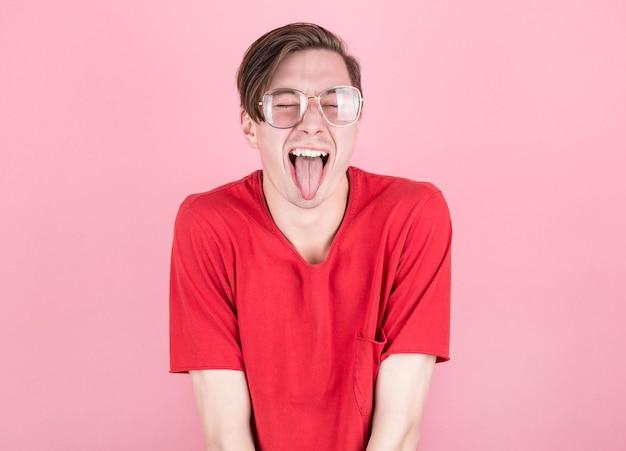 Man in rood t-shirt en bril toont tong met gesloten ogen op roze achtergrond Premium Foto