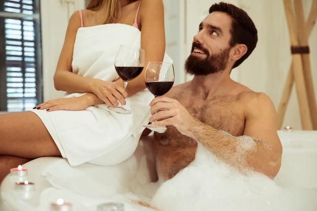 Man in spa bad met water en schuim rinkelende bril met vrouw Gratis Foto