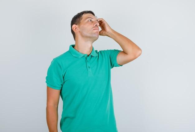 Man in t-shirt opzoeken, hand in hand en op zoek attent, vooraanzicht. Gratis Foto