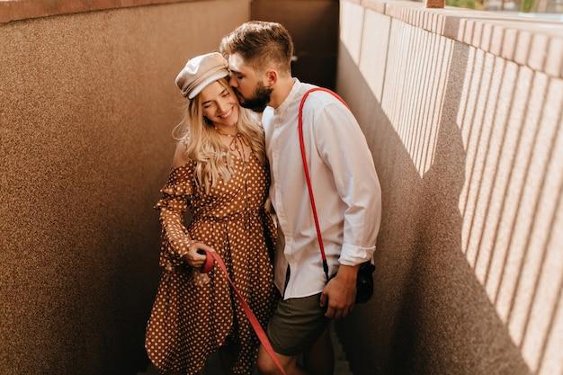 Man in wit overhemd en kaki korte broek kust zachtjes zijn positieve glimlachende blonde vrouw in bruine jurk. Gratis Foto