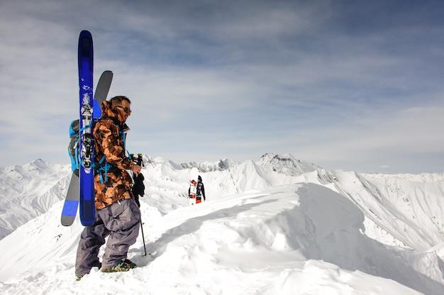 Man in zonnebril met ski en andere uitrusting rust op de top van de berg Premium Foto