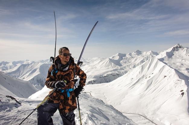 Man in zonnebril poseert met ski en andere uitrusting bovenop de berg Premium Foto