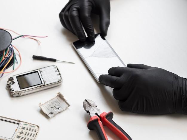 Man inspecteren telefoon met gebroken scherm Gratis Foto