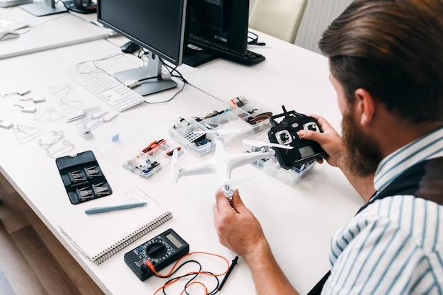 Man kijkt naar drone en afstandsbediening. ingenieur controleert verbinding tussen quodrocopter en zender voor de vlucht. testen van nieuwe elektronische apparaten Premium Foto