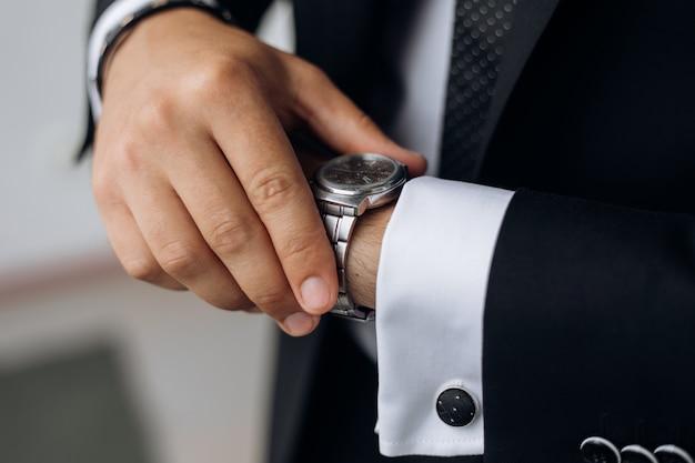 Man kijkt naar het horloge om zijn pols Gratis Foto