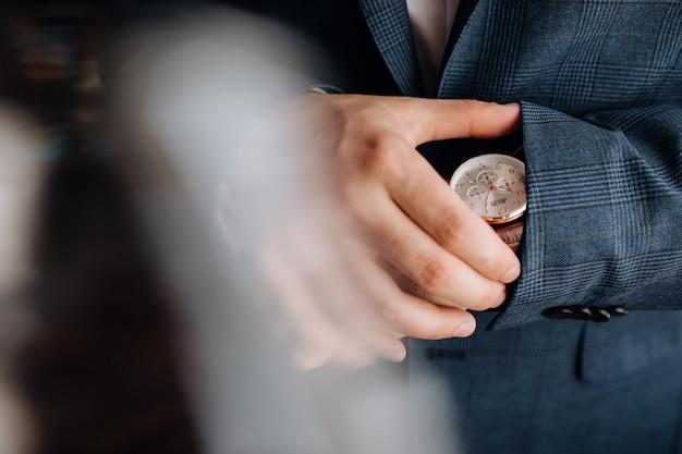 Man kijkt naar het horloge op zijn hand Gratis Foto
