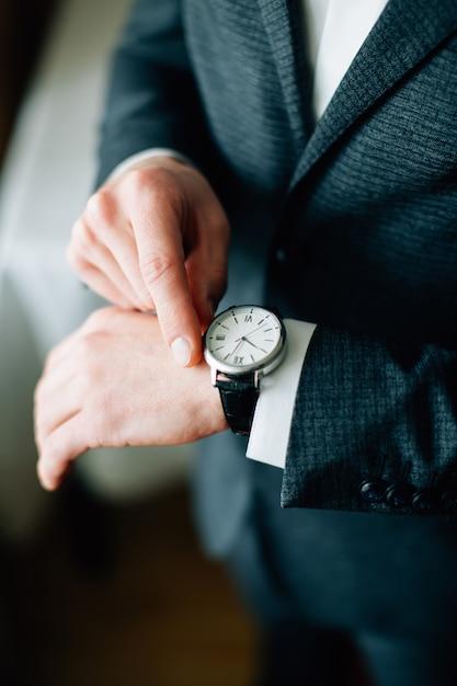 Man klaar voor werk. man met het horloge bij de hand Premium Foto
