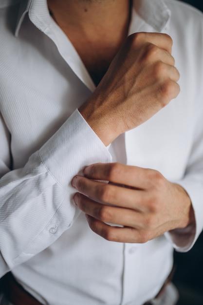 Man knoppen overhemd, een man in een wit overhemd Premium Foto