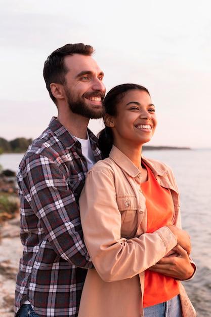 Man knuffelen zijn vriendin van achteren tijdens het kijken naar de zonsondergang Premium Foto