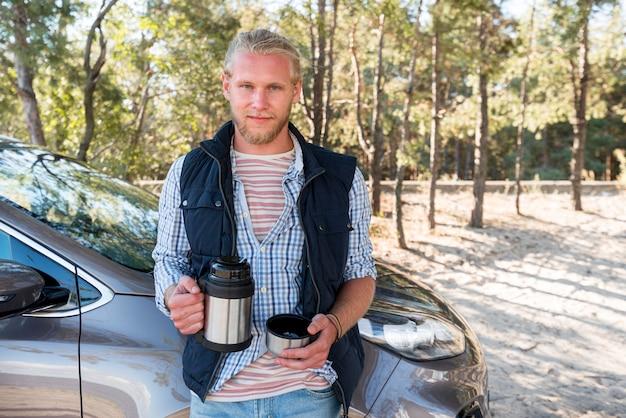 Man koffie drinken en naast auto zitten Gratis Foto