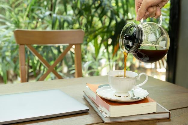 Man koffie gieten in een beker met laptop op de tafel. Premium Foto