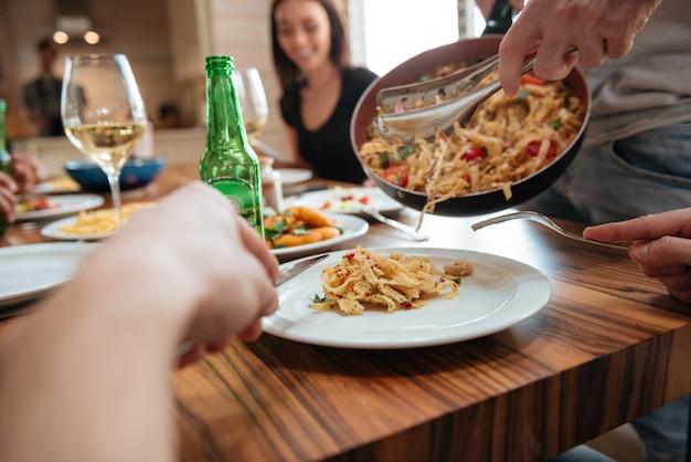 Man koken pasta en diner met vrienden aan tafel Premium Foto