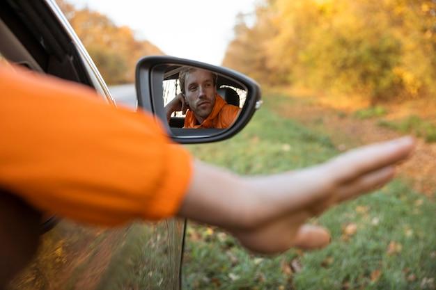 Man krijgt zijn hand uit de auto tijdens een roadtrip Gratis Foto