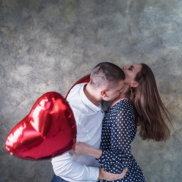 Man kussende vrouw met hartballonnen Gratis Foto