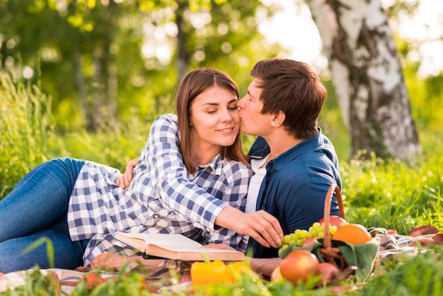 Man kussende vrouw op wang in bos Gratis Foto