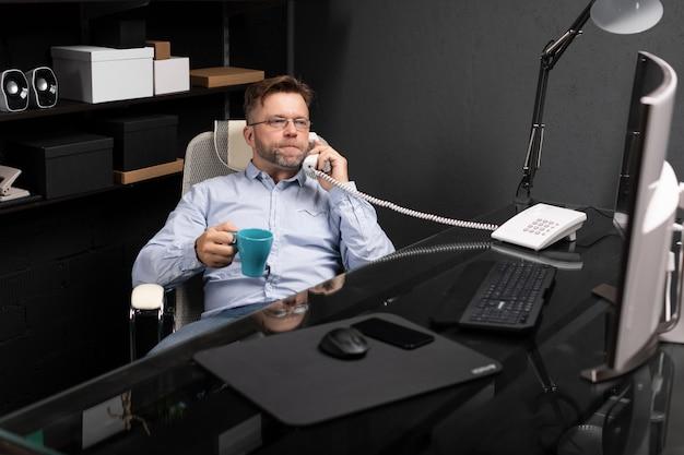 Man leunde achterover in zijn stoel, dronk koffie en praatte over de vaste lijn Premium Foto
