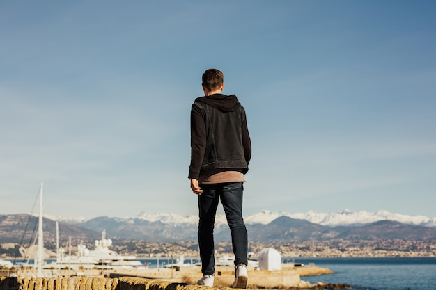 Man loopt langs de waterkant en genietend van het uitzicht op de zee. Premium Foto