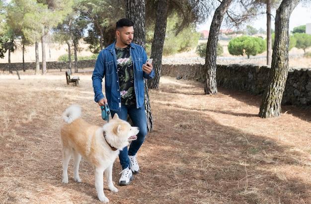 Man loopt met zijn hond in het bos Premium Foto
