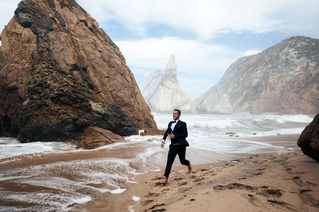 Man loopt op het natte zand tussen de rotsen Gratis Foto