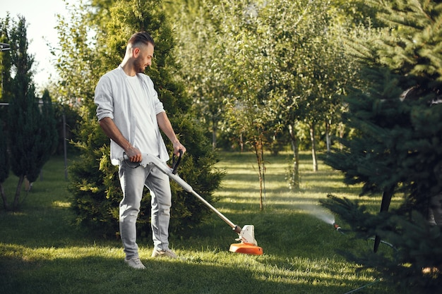 Man maaien gras met gazonverhuizer in de achtertuin. mannetje in een overhemd. Gratis Foto