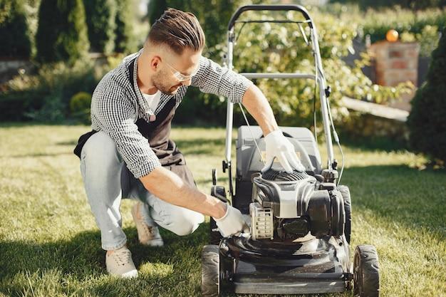 Man maaien gras met gazonverhuizer in de achtertuin. mannetje in een zwart schort. kerel repareert. Gratis Foto